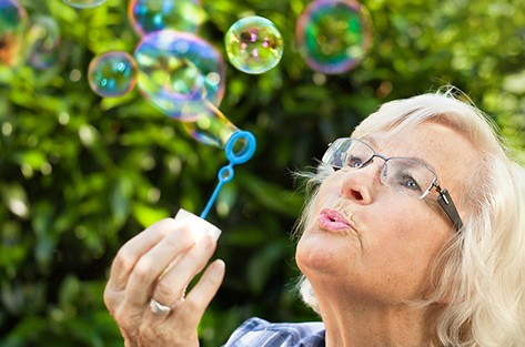 bigstock-Senior-woman-is-blowing-bubble-33764306