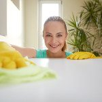 people, housework and housekeeping concept - happy woman cleaning table at home kitchen