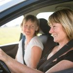 Smiling senior woman driving car with her adult child